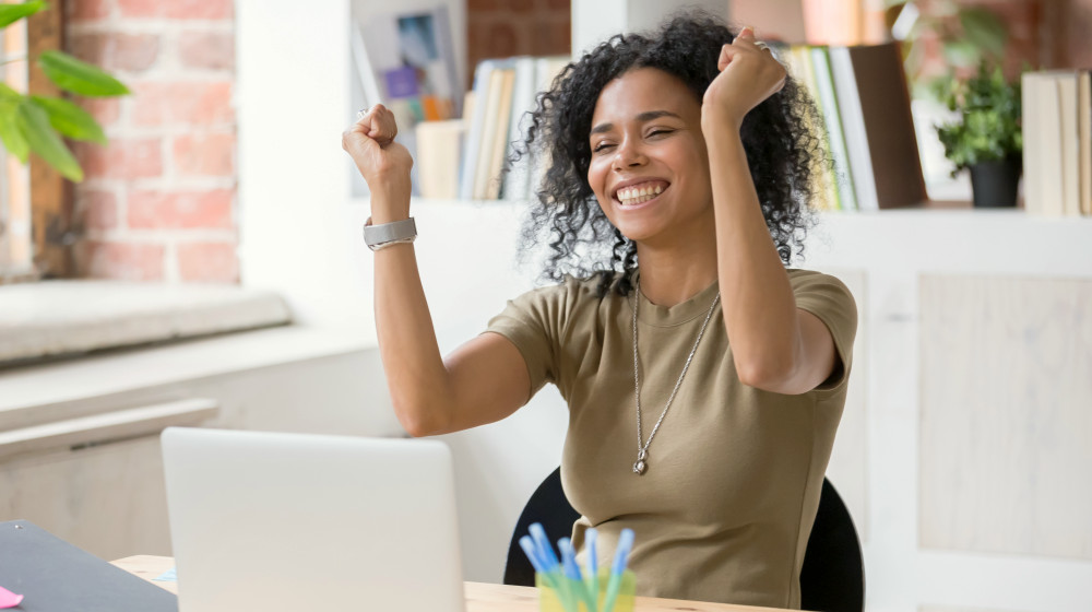 Excited African American woman sit at desk feel euphoric | Ways To Banish Holiday Stress At Work | dealing with holiday stress | Featured