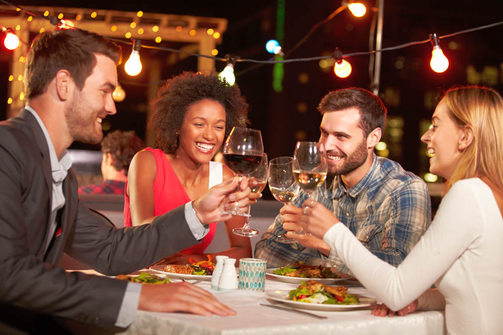 Four friends eating dinner at rooftop restaurant | How To Cheer Someone Up: Simple Ways | night owl paper goods