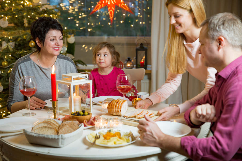 Happy family celebrating holiday together, sitting around decorated round table | How To Manage Your Holiday Finances | holiday finance | holiday budget