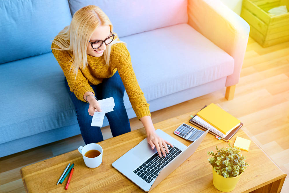 Happy young woman paying bills on laptop sitting on sofa | How To Manage Your Holiday Finances | holiday finance | holiday budgeting