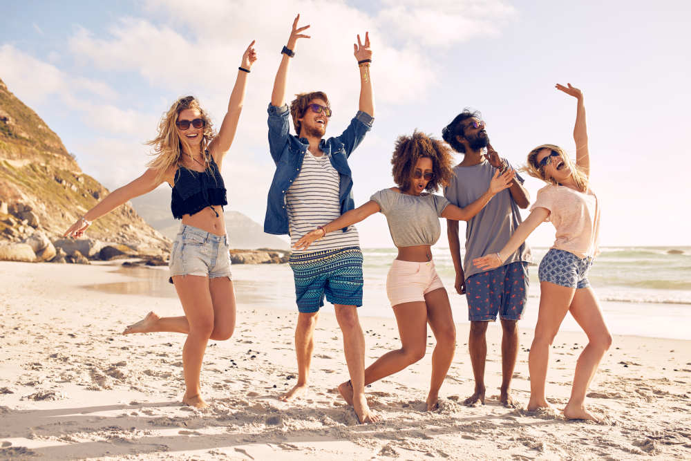 Portrait of excited young friends standing on the beach | How To Cheer Someone Up: Simple Ways | thought