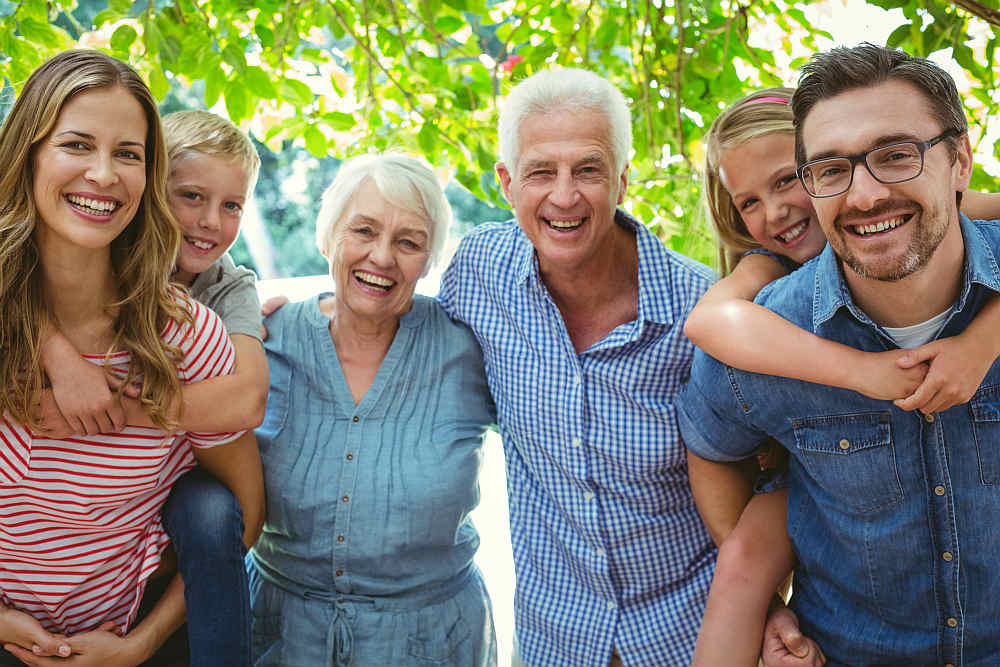 Portrait of smiling family with grandparents standing against tree | Powerful Quotes By The Nation's Most Powerful People | motivational quotes