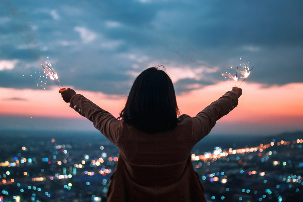 Women with sparklers in their hands that bokeh cities background | Sources of Holiday Stress And How To Beat Them | holiday stress tips