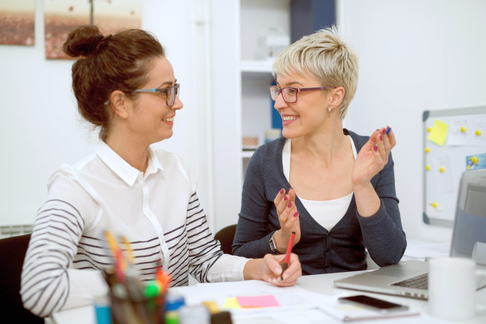 Two smiling stylish business middle aged women working and having a conversation while sitting | How To Cultivate A Meaningful Human Connection With Anyone | how to get people to like you