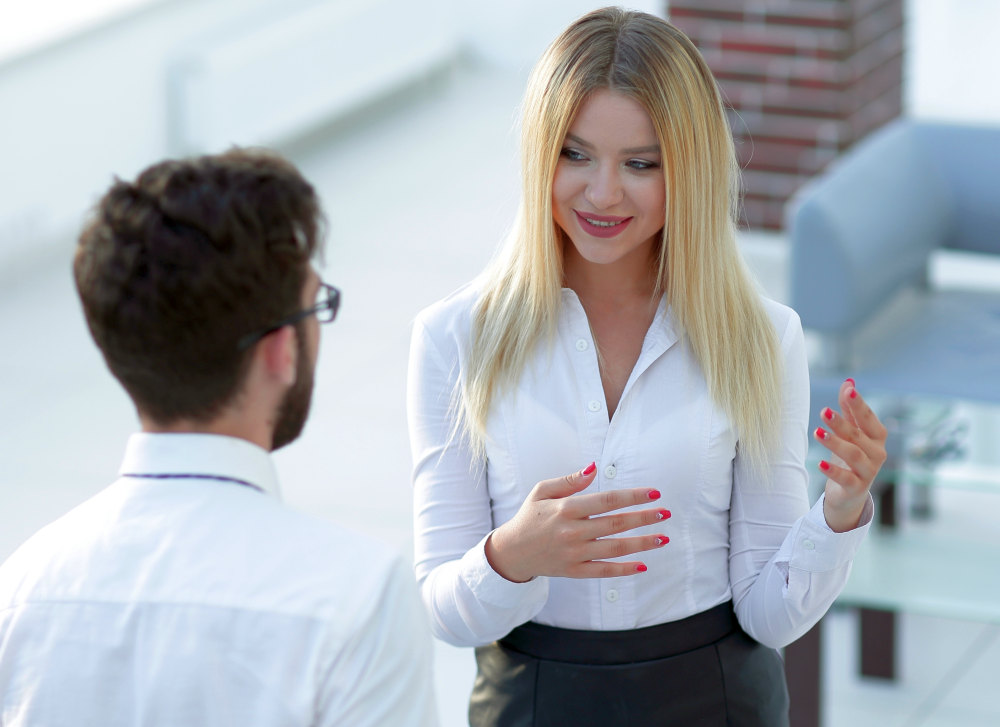 Business woman talking with a colleague | How To Be A Better Conversationalist | how to become a better conversationalist