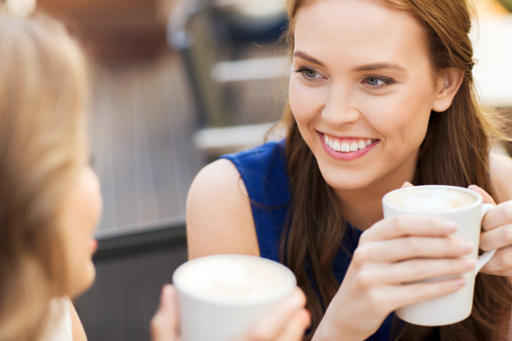 Smiling young women with coffee cups at cafe | How To Cultivate A Meaningful Human Connection With Anyone | questions to start a conversation
