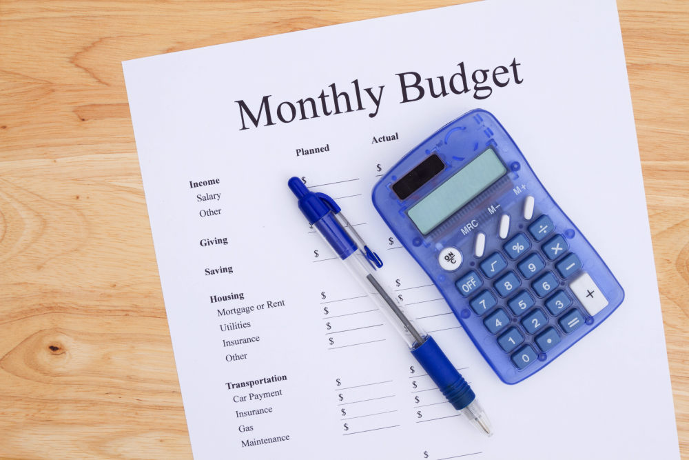A print out of a monthly budget with pen and calculator on a desk | Debt-Free Living: Tips On How To Get Out Of Debt Fast | debt free living | best way to get out of debt