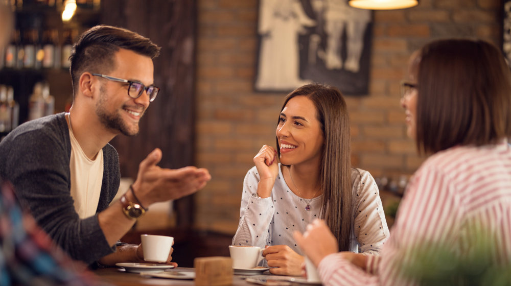 Group of happy friends drinking coffee and talking in coffee shop | How To Cultivate A Meaningful Human Connection With Anyone | how to start a good conversation | Featured