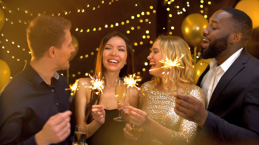 Happy group of friends holding bengal lights and wine glasses | How To Beat The Holiday Blues And Avoid Christmas Depression | post christmas blues | Featured
