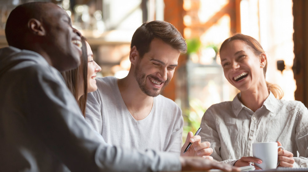 Happy multiracial young friends relax together talking laughing sit at cafe table | How To Cultivate A Meaningful Human Connection With Anyone | topics to start a conversation