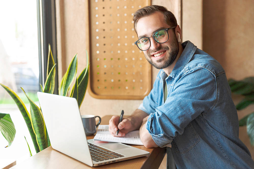 Attractive smiling man wearing glasses writing and using earpod with laptop | How To Write A Gratitude List To Start Your Day Off Strong | how to start a gratitude journal
