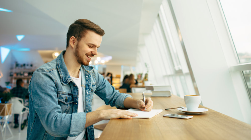 Smiling man is sitting in front of the table near window | How To Write A Gratitude List To Start Your Day Off Strong | daily gratitude list | Featured