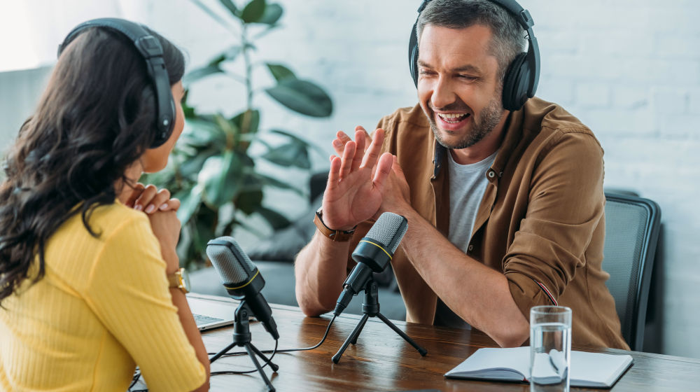 Cheerful radio host showing no sign while recording podcast with colleague | Best Motivational Podcasts That Uplift The Soul | top motivational podcasts | Featured