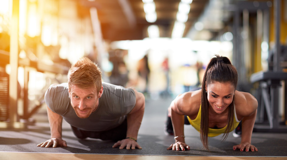 Couple doing pushups at training in gym | Fitness Challenges To Promote Overall Health & Fitness | fitness challenge ideas | Featured