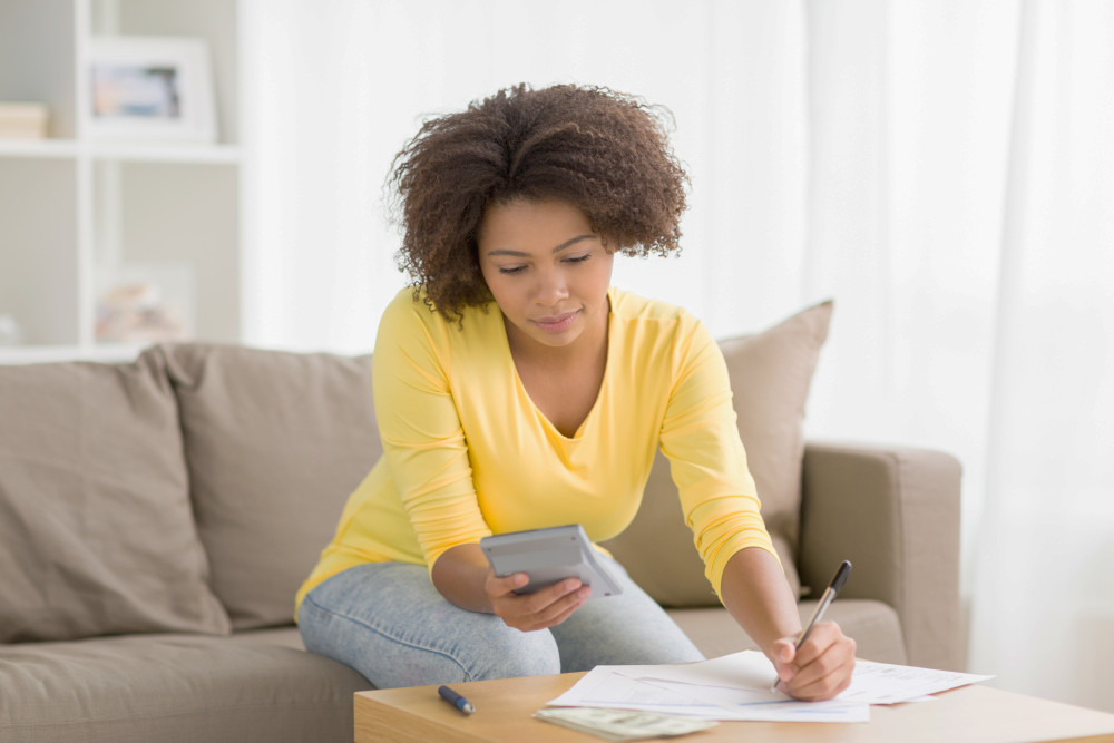 African american woman with papers and calculator counting money at home | Detail-Oriented Person: What Are The Advantages? | what is detail oriented