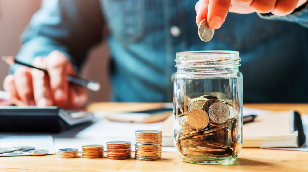 Businessman holding coins putting in glass | Priceless Pieces of Money Advice From Famous People in History | personal finance advice | Featured