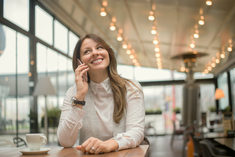 Charming woman calling with cell telephone while sitting in coffee shop | How To Manage Expenditure Better To Save More | spend less money