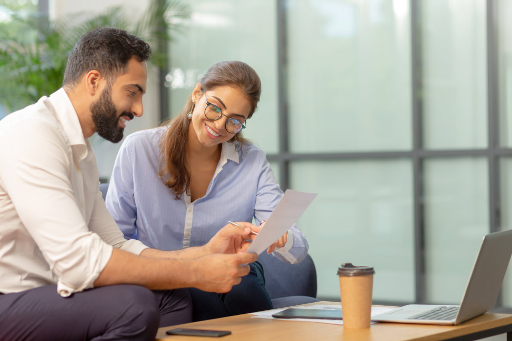 Pleased bearded man sitting in semi position while working at business plan | Helpful Ways To Improve Work Performance | Skills to improve work performance