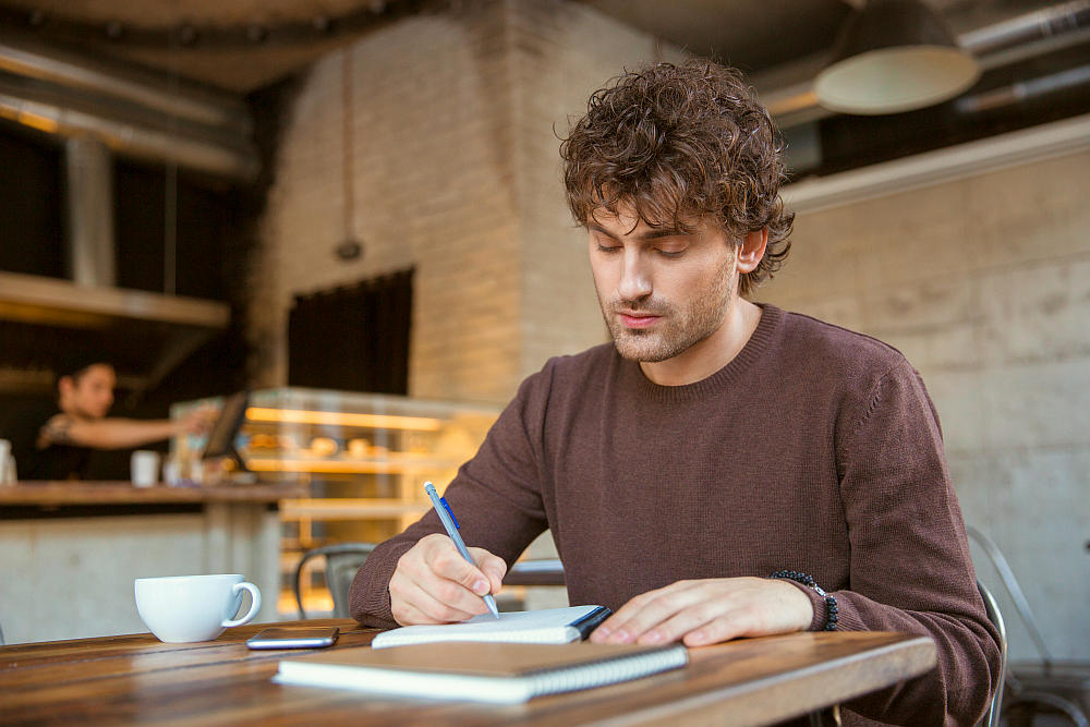 Concentrated thoughtful handsome attractive curly guy writing on a notebook | How To Be A Better Writer: Practical Tips From Famous Authors | how to be a better writer essay