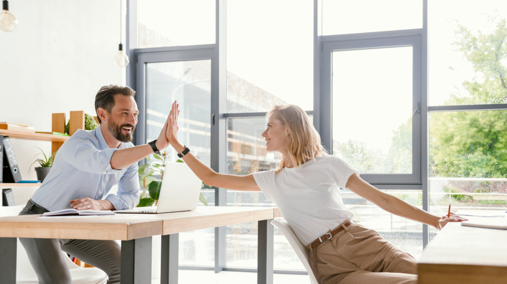Couple of happy colleagues giving high five while sitting at the office | Ways You Can Pass On Positive Vibes To Other People | sending positive vibes your way | Featured