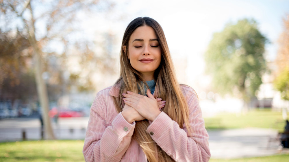 Faithful woman closes eyes and keeps hands on chest near heart | Reasons Why People Should Have The Attitude Of Gratitude | words of gratitude | Featured