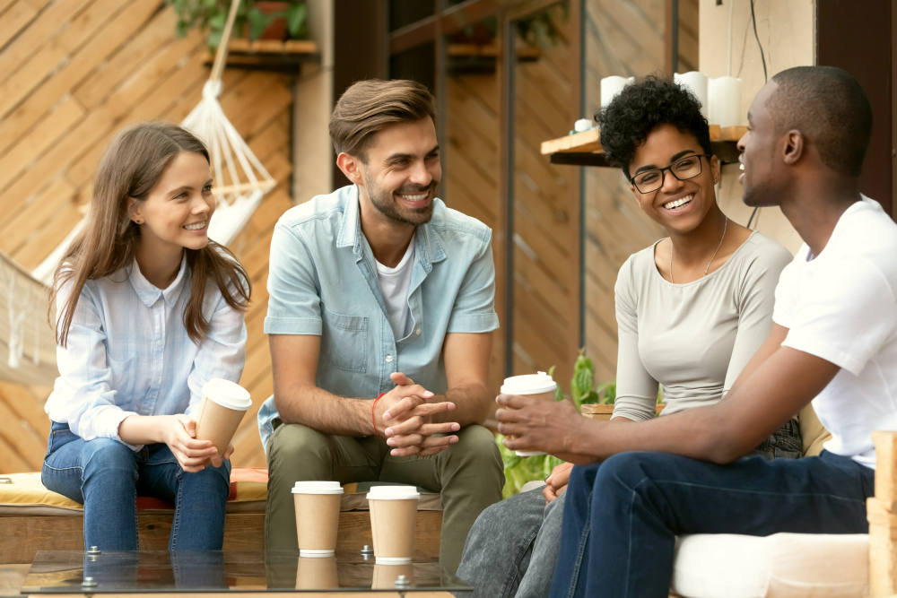 Four laughing diverse people positive multi-ethnic friends sitting in cozy cafe | How To Be A Better Friend And Forge Meaningful Relationships | ways to be a good friend