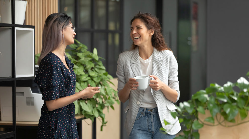 Happy positive female colleagues joking laughing during coffee break | Ways You Can Pass On Positive Vibes To Other People | positive mind positive vibes positive life