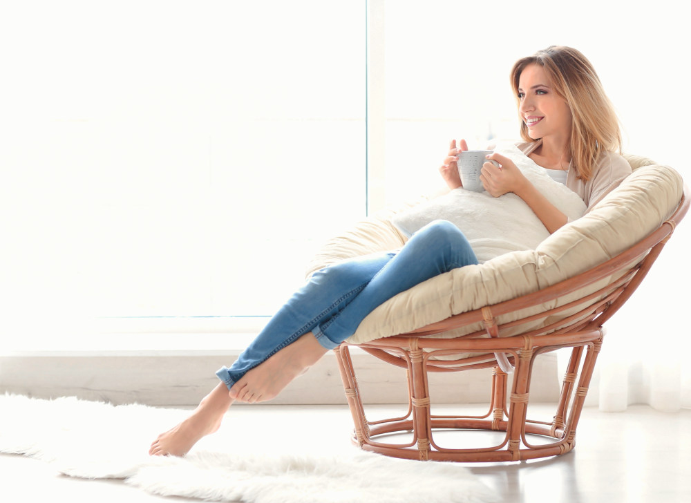 Happy young woman drinking tea while sitting in armchair at home | Self-Care Quotes And Tips From Famous Celebrities | self care quotes | quotes about self care