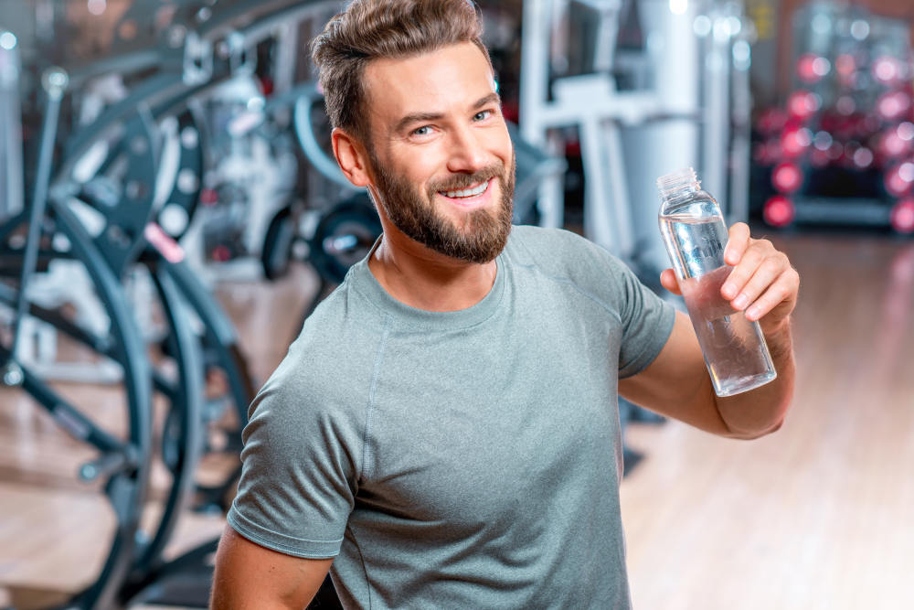 Handsome muscular man drinking water in the gym | Fitness Challenges To Promote Overall Health & Fitness | workout challenges