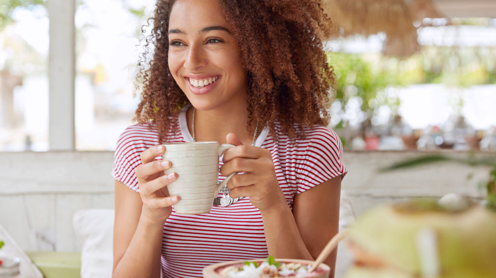 Positive dark skinned mixed race female enjoys good rest at coffee shop | Self-Care Quotes And Tips From Famous Celebrities | self care quotes | self care | Featured