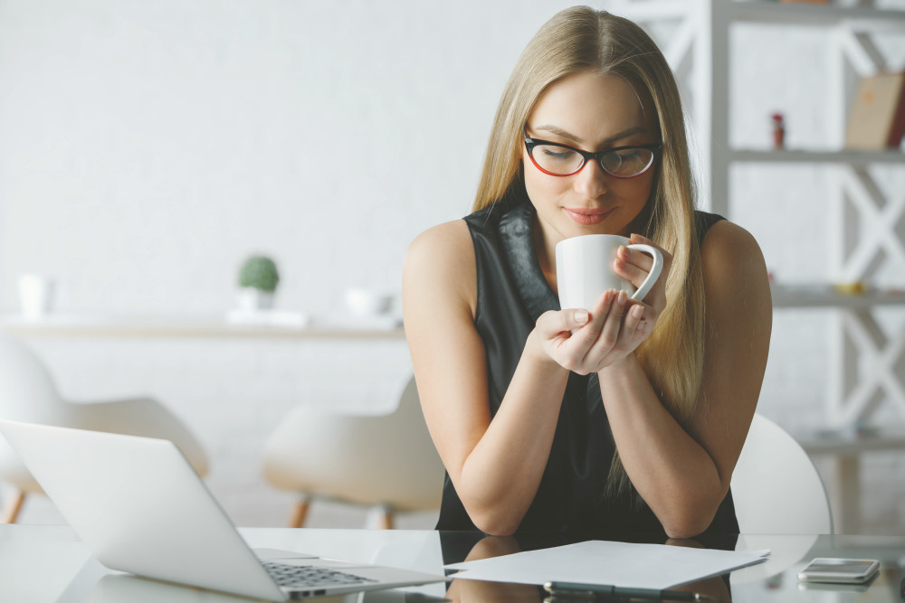 Smiling young woman drinking coffee at modern office desk   The Early Bird Gets The Worm: Reasons People Wake Up Early   waking up early
