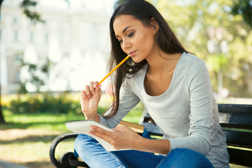 Thoughtful woman sitting on the bench with pen and notepad outdoors | How To Be A Better Writer: Practical Tips From Famous Authors | how to be a better creative writer