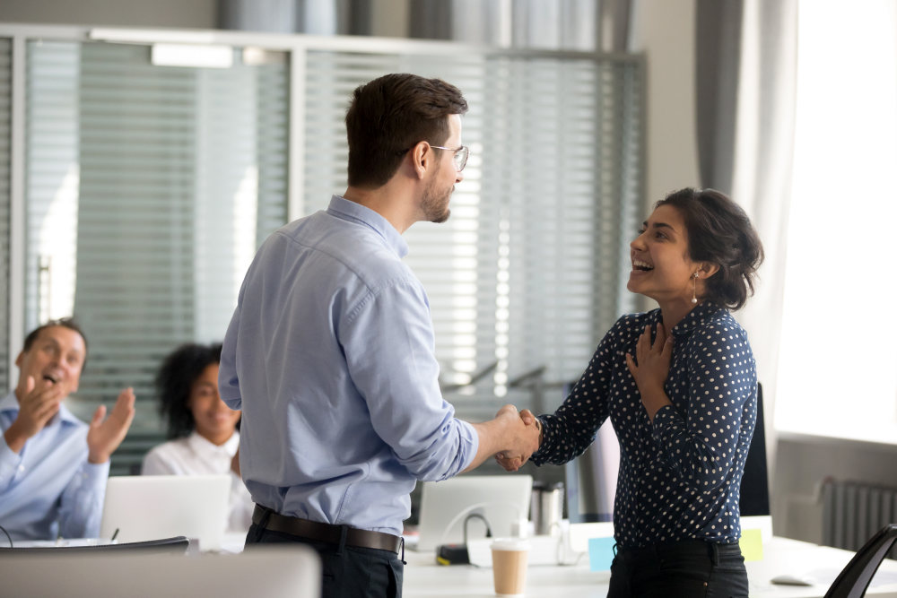 Team leader motivating handshaking female Indian excited employee | Ways You Can Pass On Positive Vibes To Other People | positive vibes only