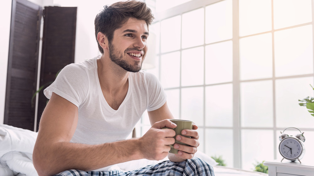 man wakes up sitting on bed drinking coffee having a wonderful morning | The Early Bird Gets The Worm: Reasons People Wake Up Early | early bird catches the worm | Featured