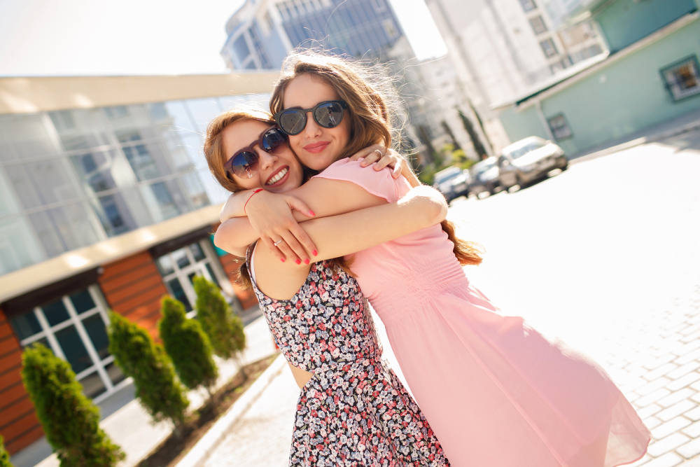 Two girls friends laughing and hugging | How Being Kind-Hearted Makes People Healthier | kindness and health | kind hearted