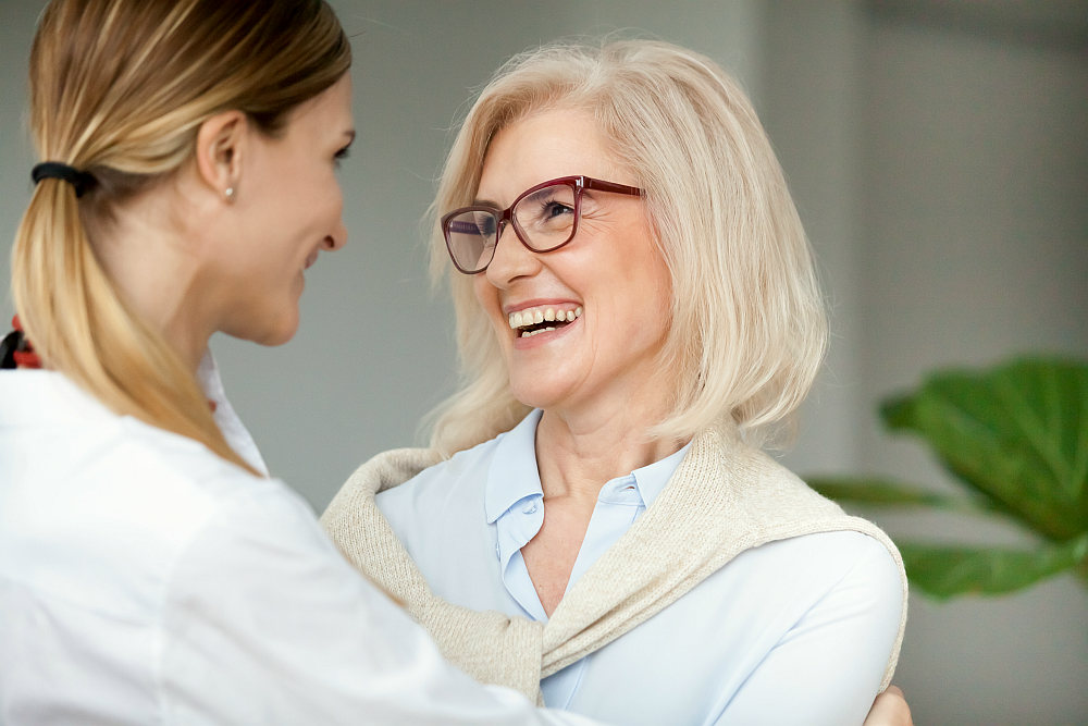 Beautiful aged woman in glasses embracing young adult lady and laughing | Self Discovery Journal Prompts to Help You Start Writing | journaling pdf