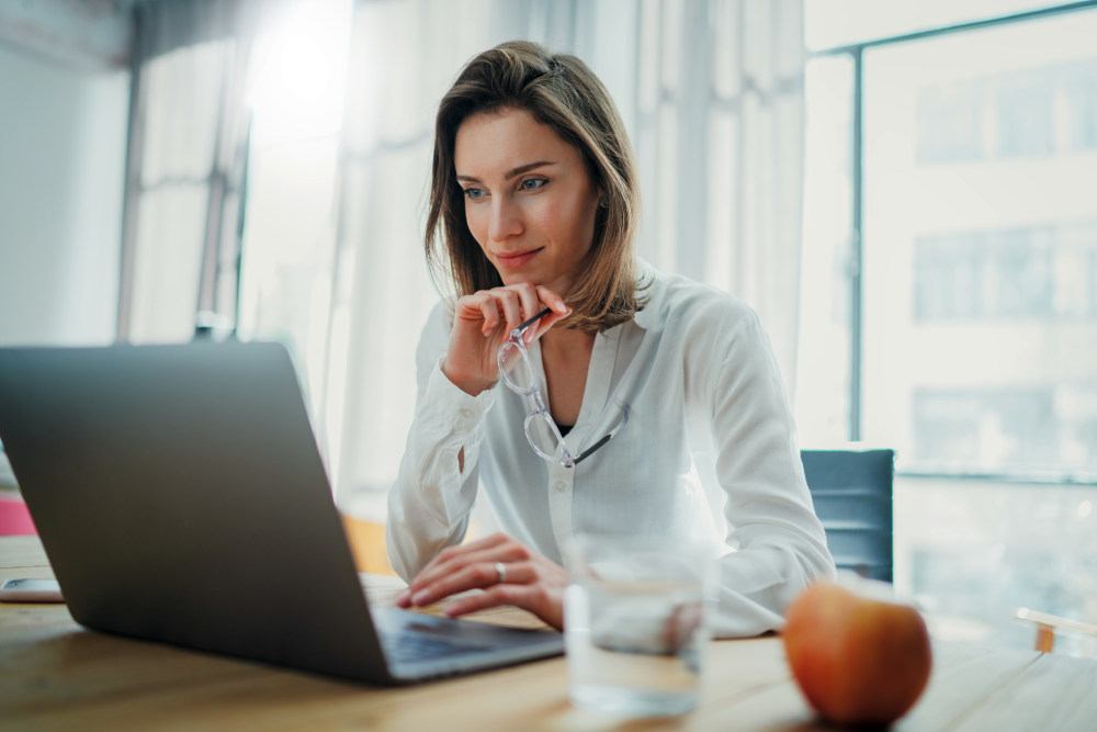 Confident businesswoman working on laptop at her workplace | Moving On After A Breakup: Effective Ways | quotes about moving on