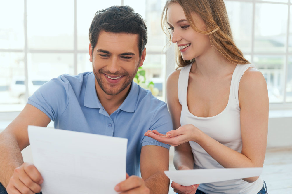 Cheerful young couple examining documents while sitting close to each other   How To Be A Better Wife: Practical Tips   how to be a better christian wife