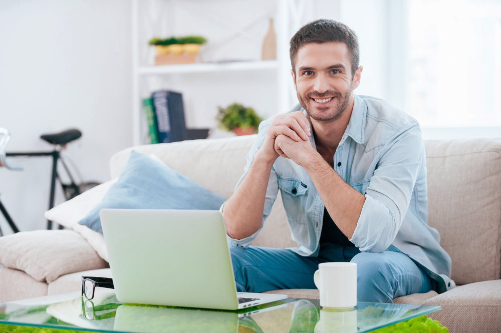 Handsome young man looking at camera and smiling while sitting on the couch at home with laptop laying near him | How To Survive Quarter Life Crisis In Your 20s | quarter life crisis books