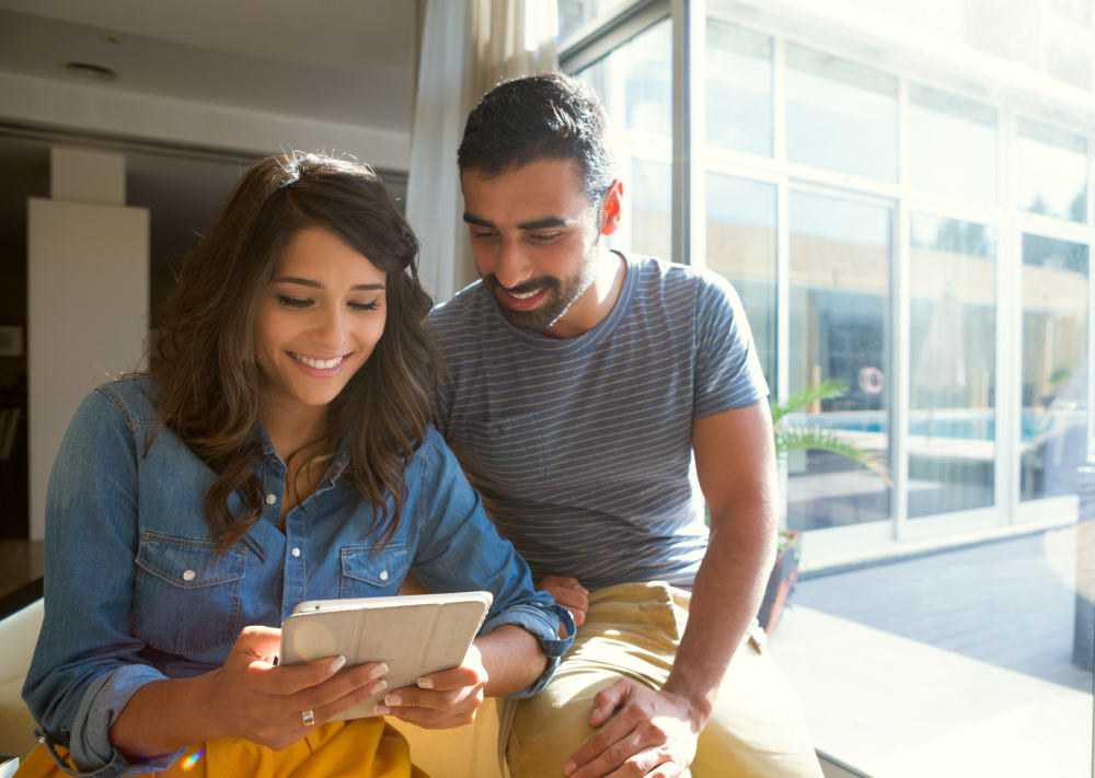 Fashion couple using a tablet with sunbeams   Better Money Habits You Can Build This Year   money habits