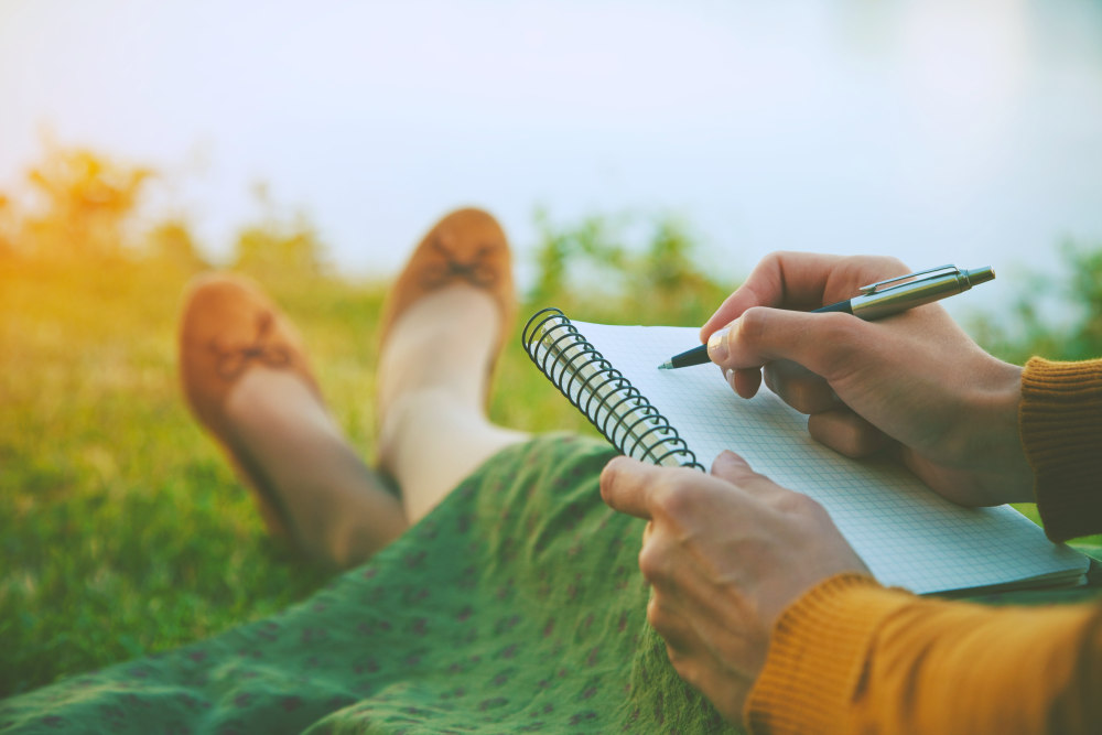 Female hands with pen writing on notebook on grass outside | Self Discovery Journal Prompts to Help You Start Writing  | journal prompts pdf