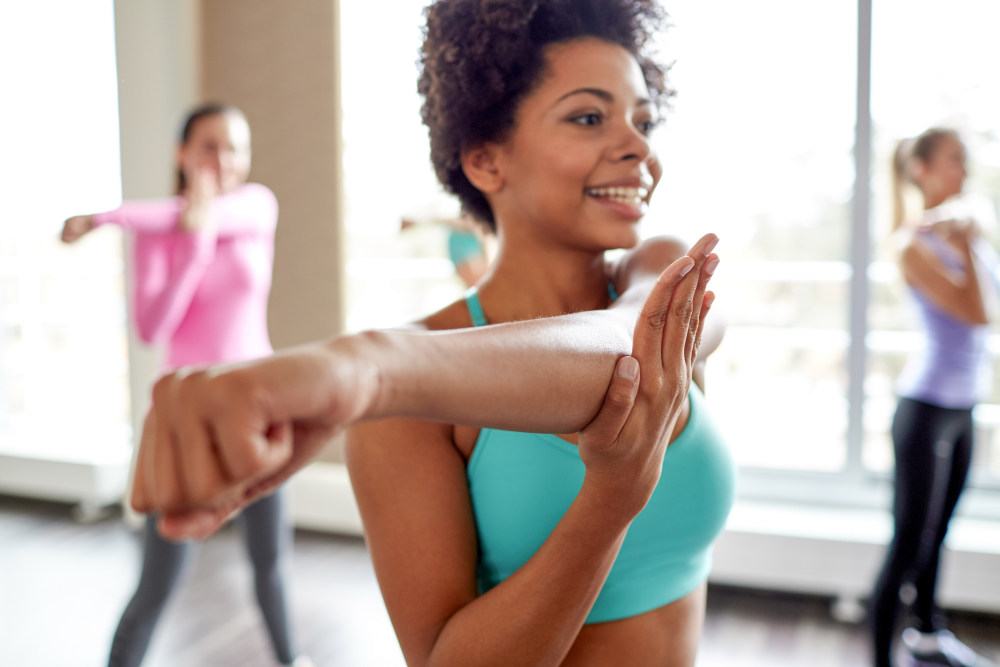 Smiling african american woman with group of women stretching arms in the gym   The Art of Aging Gracefully: Practical Ways To Do   anti-aging tips