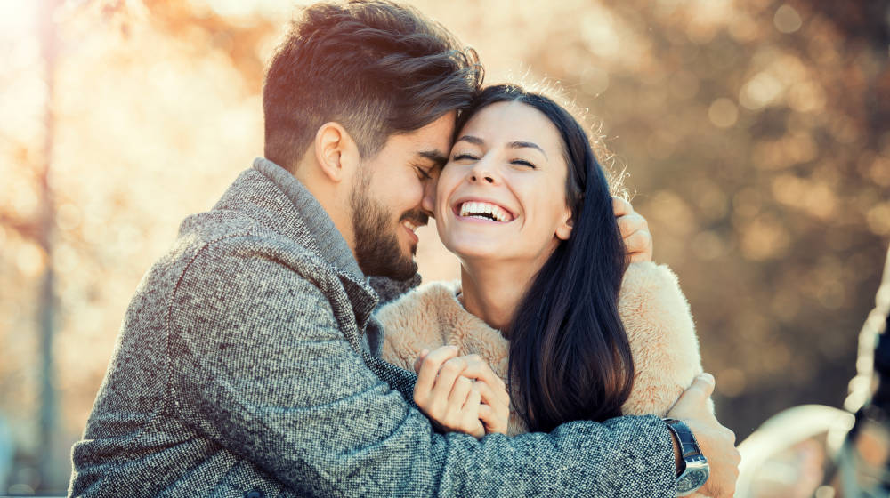 Happy young couple hugging and laughing outdoors | How To Improve Your Marriage In Simple Ways | how to improve marriage | Featured