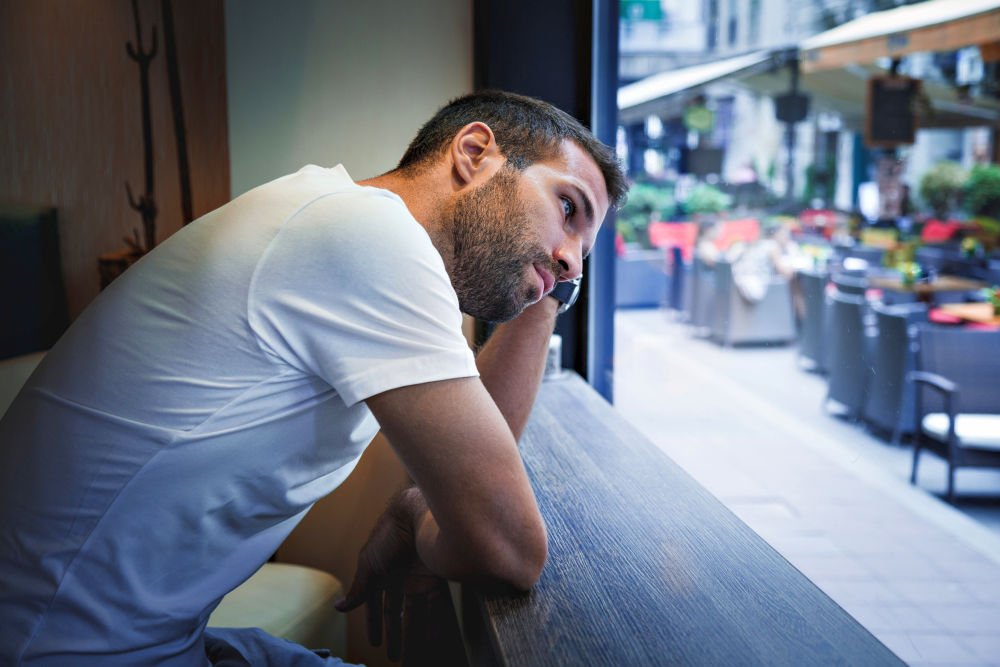 Man thinking by the bar window | Moving On After A Breakup: Effective Ways | songs about moving on