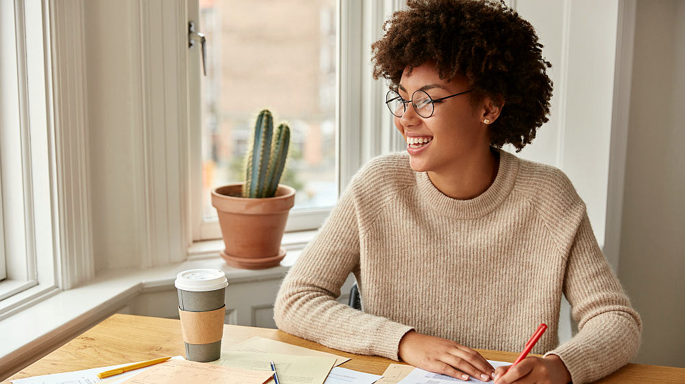 Optimistic clever freelancer notices something funny at window   Simple Ways To Become An Optimistic Person in 2020   what is an optimistic person   Featured