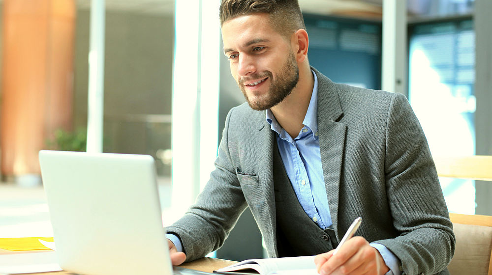 Portrait of young man sitting at his desk in the office | How To Set Achievable Short Term Career Goals for 2020 | short term goals | short term and long term goals | Featured