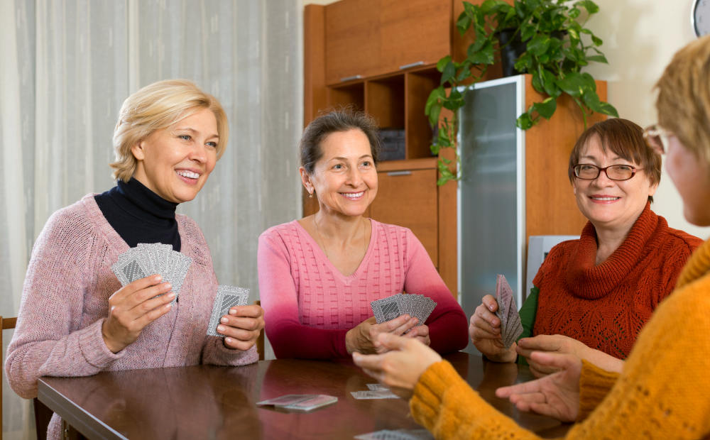 Positive smiling senior women playing cards at home   The Art of Aging Gracefully: Practical Ways To Do   secrets of aging gracefully