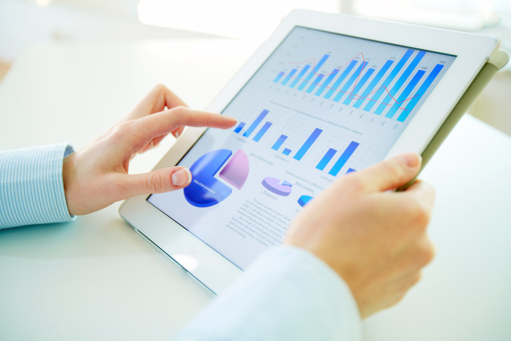 Business person analyzing financial statistics displayed on the tablet screen | Corporate Development Tips from Famous Professionals | what is corporate development