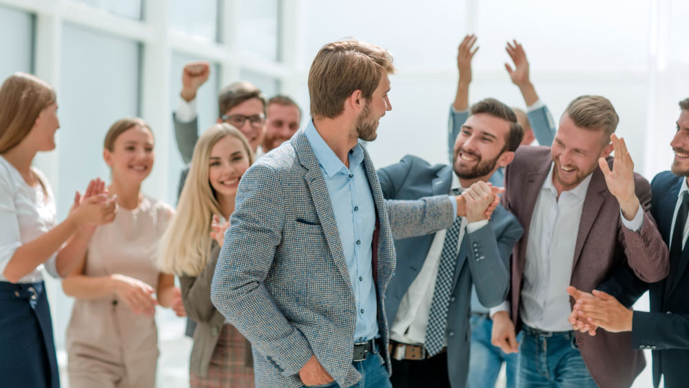 Cheerful employees congratulating a colleague on the promotion | Inspiring Movies That Can Change Your Life | most inspiring movies