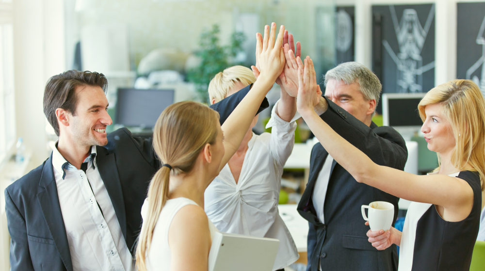 Happy business team making high five with their hands in the office | Motivational Sales Quotes That Will Fire Up Your Team | sales motivation | motivation quotes for sales | Featured